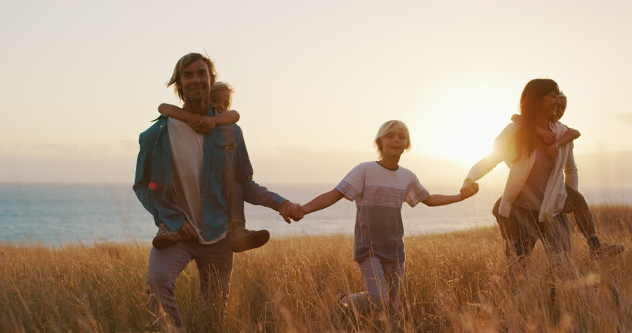 Happy smiling family holding hands walking through golden field at sunset by the ocean, piggy back ride #1024118159