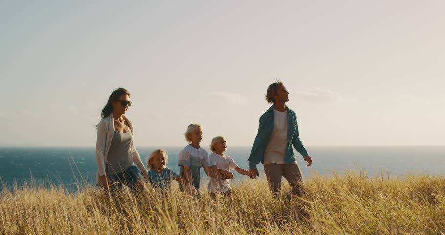 Happy smiling family walking holding hands in golden field near the ocean at sunset #1024118162