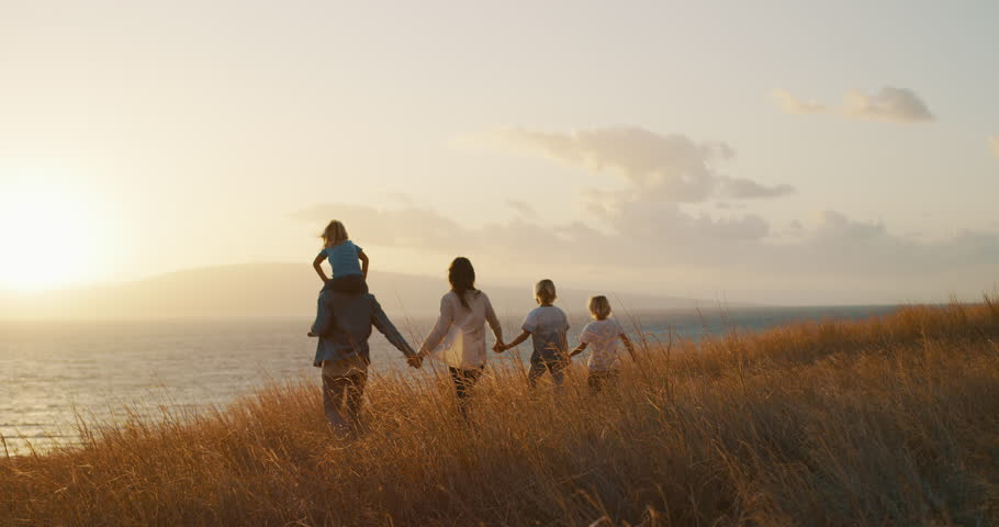 Happy family walking in golden field and looking out to the sunset together by the ocean #1024118171