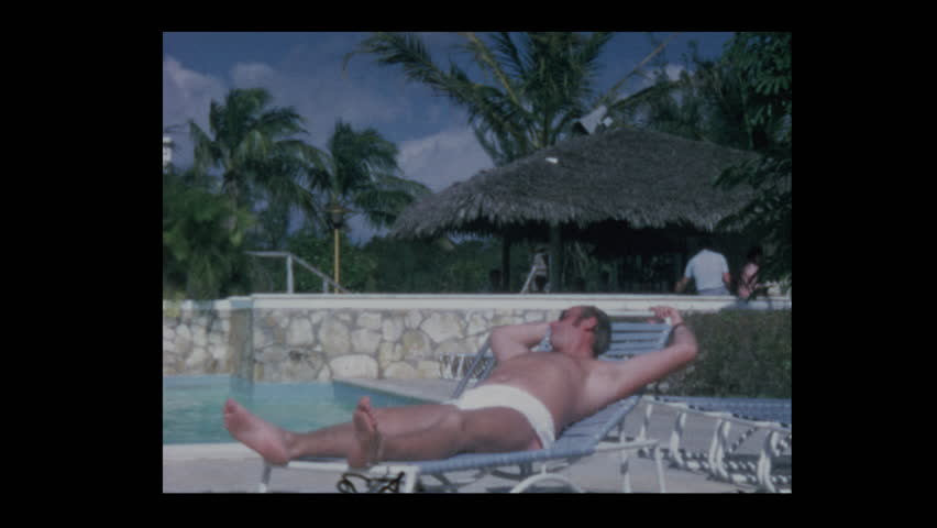 Nassau, Bahamas - 1971: People on vacation relax by the water at hotel