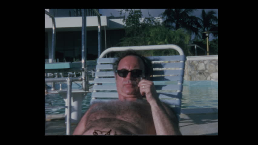 Nassau, Bahamas - 1971: People lounge by hotel resort pool