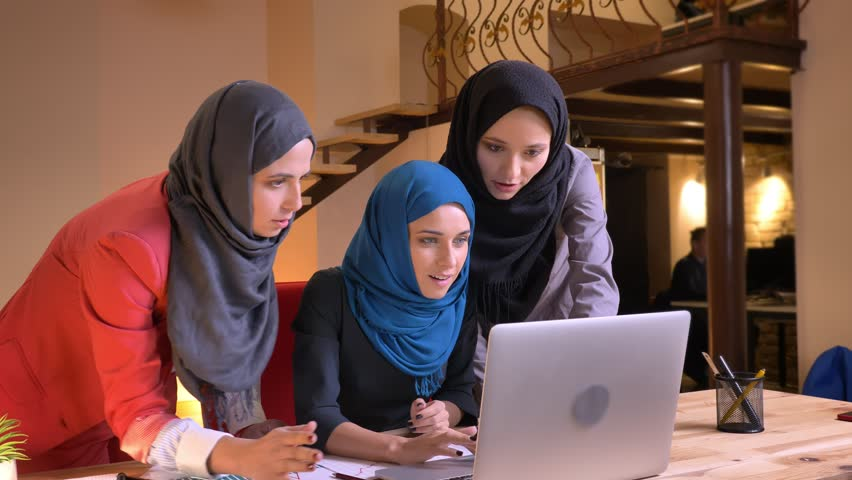 Closeup shoot of three friendly muslim female office workers checking on the laptop and getting happy and excited indoors on the workplace