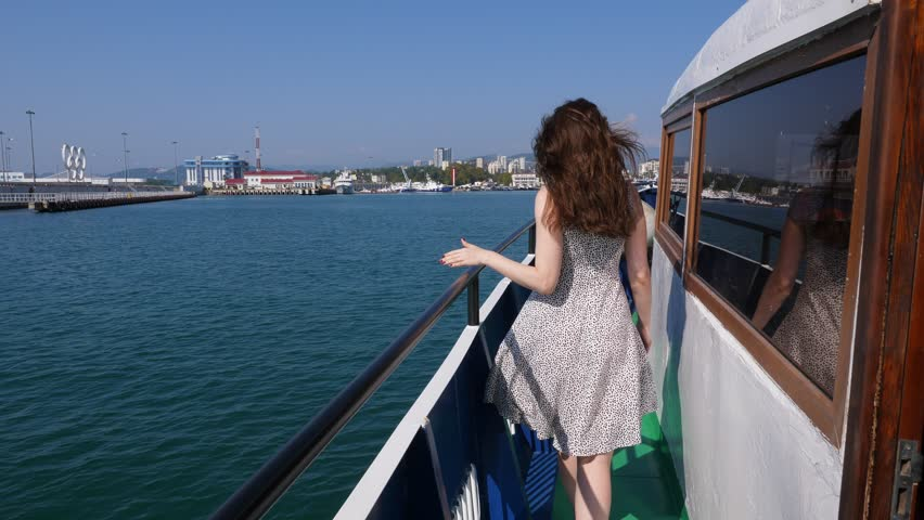 Cheerful woman run along old ship deck to bow, enjoy sunny weather and nice sea trip. Long hair and light dress fly on wind, slow motion shot, POV follow camera. City port seen ahead | Shutterstock HD Video #1024191575