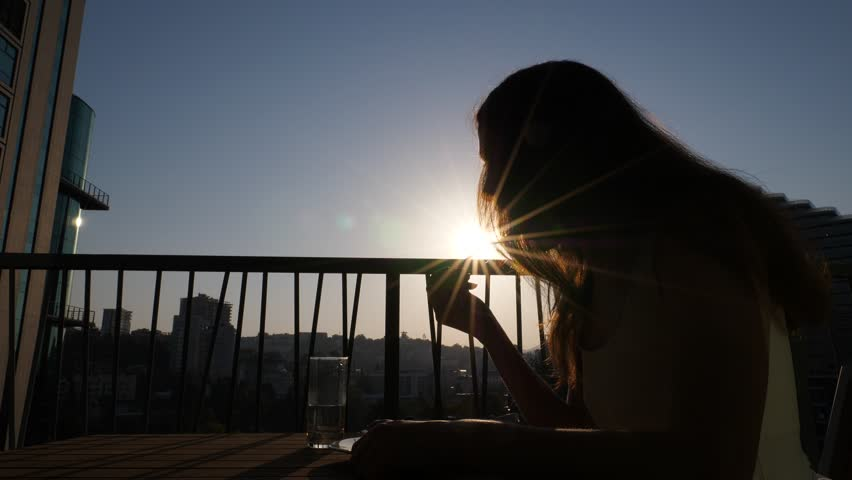 Woman have light breakfast on balcony, eat green leaf of salad, bright sun shine straight, shadow silhouette of brunette. Lady eat healthy food at morning hour | Shutterstock HD Video #1024191977