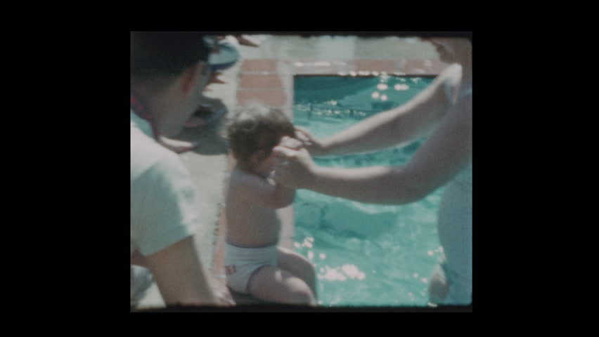 Baltimore, Maryland, USA - 1958: Woman dips baby girl in pool