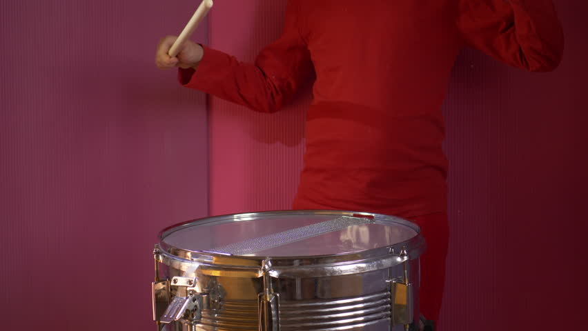 Teen boy in red suit playing drum in rain. child holds drumsticks. Drops of water fall on drum. Splashes fly in different directions.