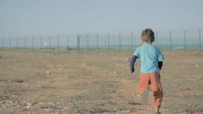 One happy running little boy refugee among desert near border in sunny day. concept way to freedom   Shutterstock HD Video #1024233833