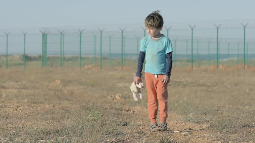 Lonely sad boy orphan walking along the abandoned road with head down in the hands of holding a toy rabbit stopping and looking into the distance. concept of immigration and refugee camp   Shutterstock HD Video #1024233950