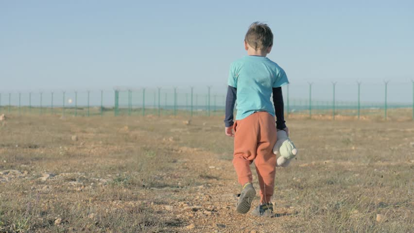 Lonely tired little boy with a plush toy in his hand moves towards the border. concept child immigration and refugees   Shutterstock HD Video #1024233953