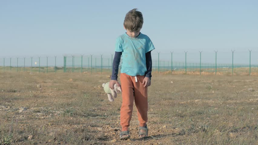 Orphan. Abandoned lonely child on area of the refugee camp. boy in dirty threadbare clothes holding toy plush bunny homeless little kid as result of war conflict. concept of depression and despair   Shutterstock HD Video #1024233956