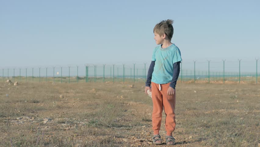 Sad little child refugee with dirt on his clothes. area of the refugee camp encircled by a high fence, poor boy holding plush bunny and looks into the distance   Shutterstock HD Video #1024233959