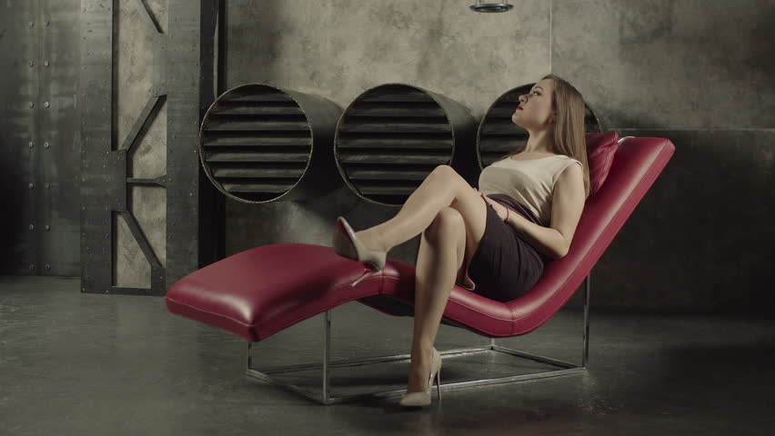 Profile of nude woman sitting on chair stock photo