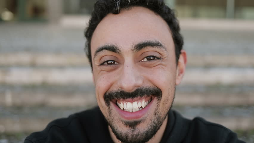 Close up shot of young Arabic mans face with dark curly hair and beard in black hoodie sitting on stairs outside, having video chat with friend, waving hand. Lifestyle, communication concept | Shutterstock HD Video #1024237793