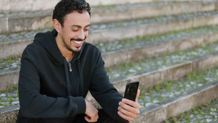 Young Arabic man with dark curly hair and beard in black hoodie sitting on stairs outside, having video chat, waving hand, showing surroundings. Lifestyle, communication concept