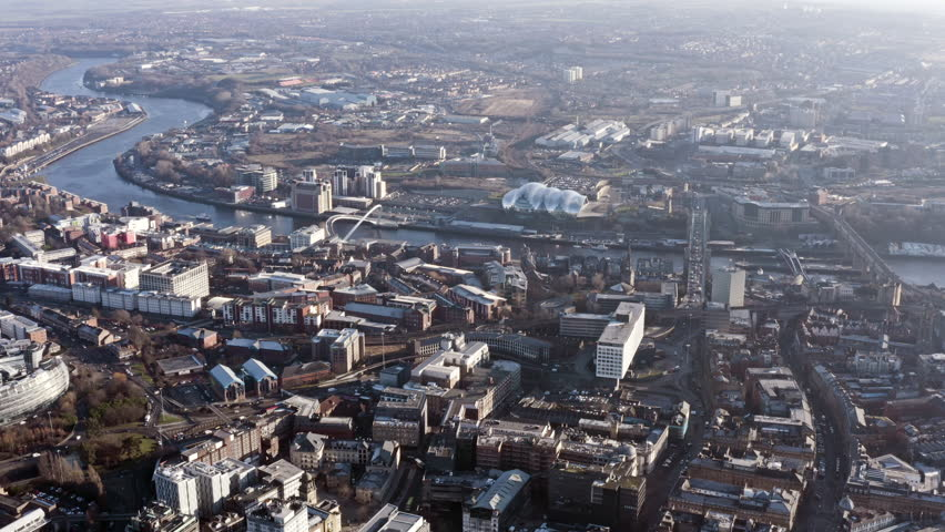 Newcastle upon Tyne aerial view is a university city on the River Tyne in northeast England flying over famous Spanning the Tyne, modern iconic landmark Gateshead Millennium Bridge in the UK - HD 4K    Shutterstock HD Video #1024239827