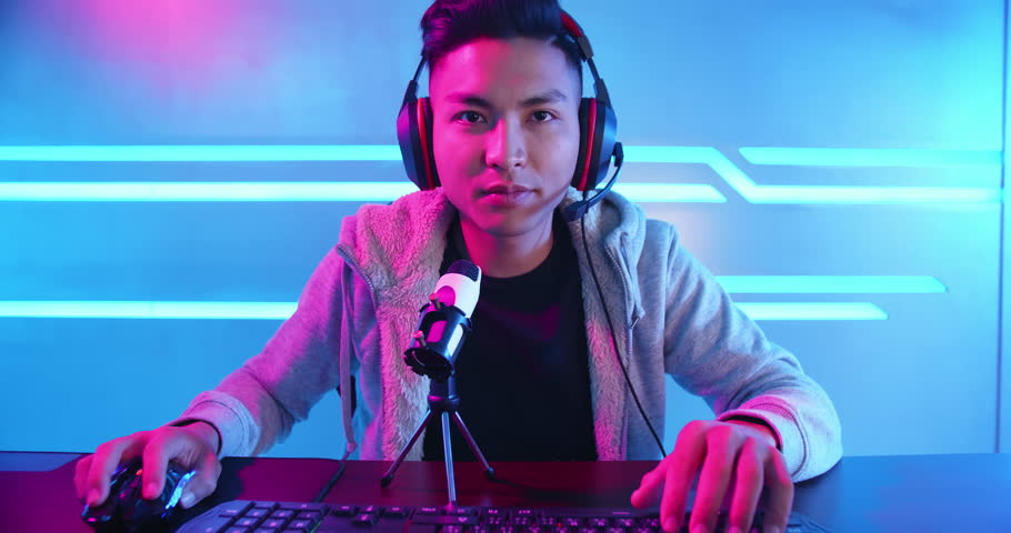 Young Asian Handsome vlogger having live stream and introduce online Video Game | Shutterstock HD Video #1024265546