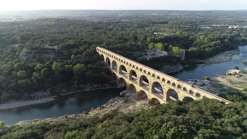 Aerial bird view footage Pont du Gard is ancient Roman aqueduct that crosses Gardon River near towns of Remoulins Avignon and Nimes in southern France it is on UNESCO's list of World Heritage Sites 4k