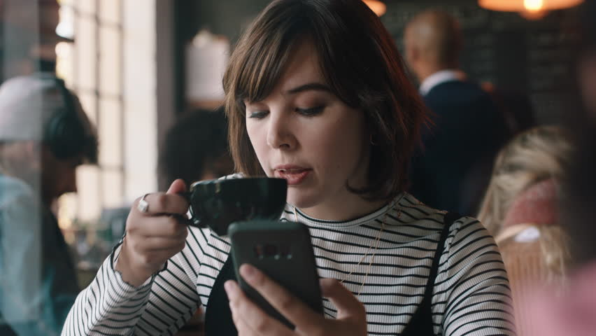 young woman using smartphone drinking coffee in cafe texting sharing messages on social media enjoying mobile technology #1024294271