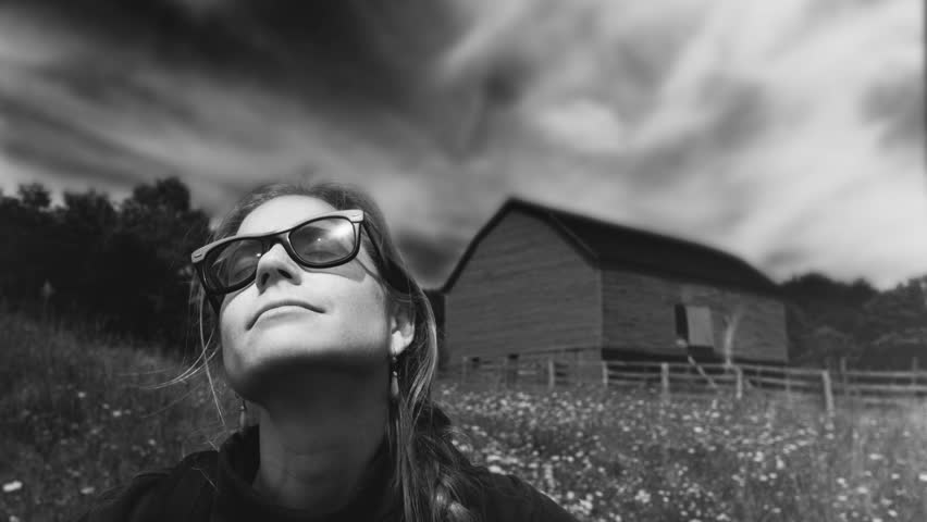 Black and white cinemagraph of a woman with her face to the sky and clouds and barn in the background. | Shutterstock HD Video #1024300094