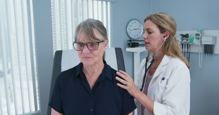 Female doctor using stethoscope listening to senior patients lungs. Older woman visiting her primary care physician for a regular check up. Slow motion 4k