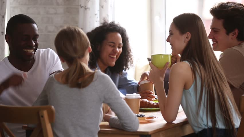 Diverse happy students talking joking having fun share cafe table at group meeting, african and caucasian young friends laughing drinking coffee tea together enjoy multiracial friendship in dormitory