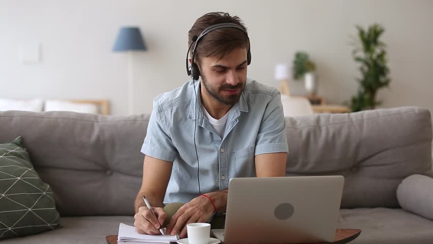 Happy young man in headset speaking by webcam looking at laptop make notes, male sales representative talking by video call study online consulting customer selling service support working from home