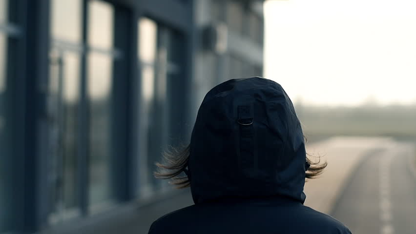 Rear view of hooded female person walking the city street in cold winter afternoon, slow motion #1024311158