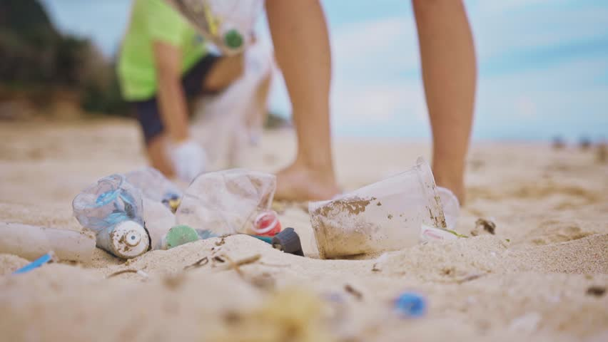 Group of volunteers cleaning up white beach. The volunteer raises and throws a plastic garbage into the bag. Volunteering and recycling concept. Environmental awareness concept copy space | Shutterstock HD Video #1024333574
