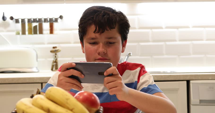 Portrait of a preteen boy with smartphone sitting in the kitchen Kid watching to screen, reading, typing, playing games   Shutterstock HD Video #1024340321