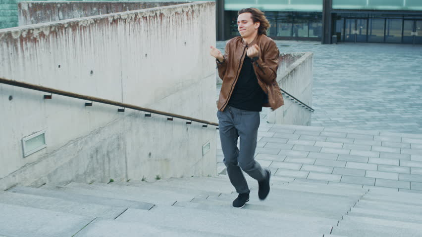 Happy Young Man with Long Hair Actively Dancing While Walking Up the Stairs. He's Wearing a Brown Leather Jacket. Scene Shot in an Urban Concrete Park Next to Business Center. | Shutterstock HD Video #1024342472