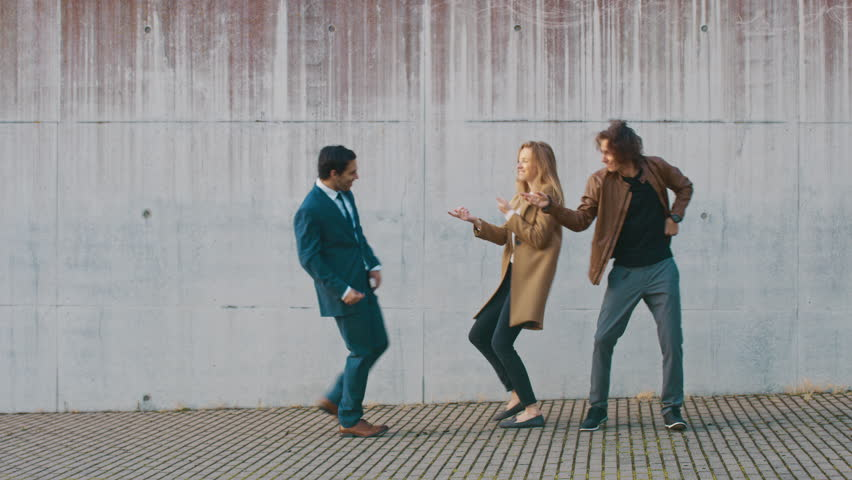 Cheerful Girl and Happy Young Man with Long Hair are Actively Dancing on a Street. Businessman in a Suit Joins Them. They Wear Brown Leather Jacket and Coat. Sunny Day. | Shutterstock HD Video #1024342499
