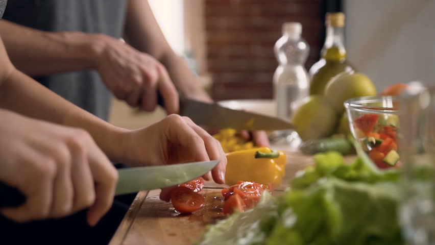 Close up shot of man hands slicing carrot and female hands cutting tomato on wooden cutting board for salad on the table with healthy food in the kitchen. Side view.