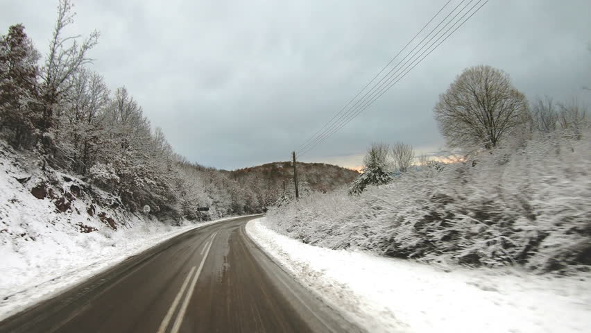 Winter Road POV from Windshield. Great shot of a slushy winter road surrounded by snow, point of view shot from the front of the car looking at the road moving
