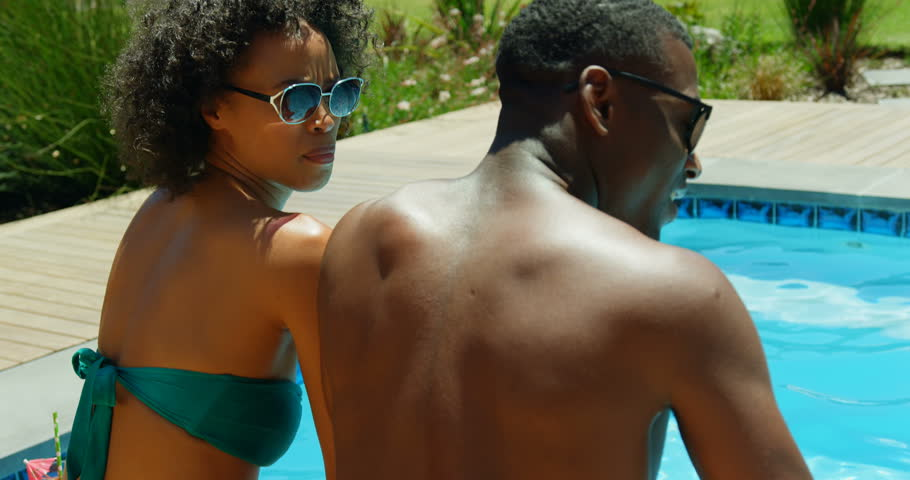 Rear view close up of African-american couple soaking their feet in swimming pool, Couple relaxing near swimming pool  | Shutterstock HD Video #1024353683