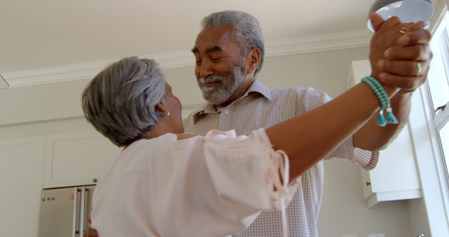 Side view of senior African-american couple dancing together in kitchen at comfortable home. They are smiling and holding hands, Social distancing and self isolation in quarantine lockdown for Covid