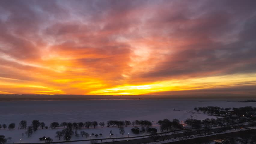 Beautiful aerial zoom out timelapse of a sunrise over Lake Michigan with orange pink and blue clouds above and snow covered lakefront with traffic along Lake Shore Drive in Chicago.