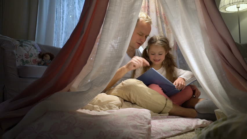 Distance learning at home. Self isolation, home quarantine. Happy family father and her little daughter having fun reading a book in a tent at home. Slow motion