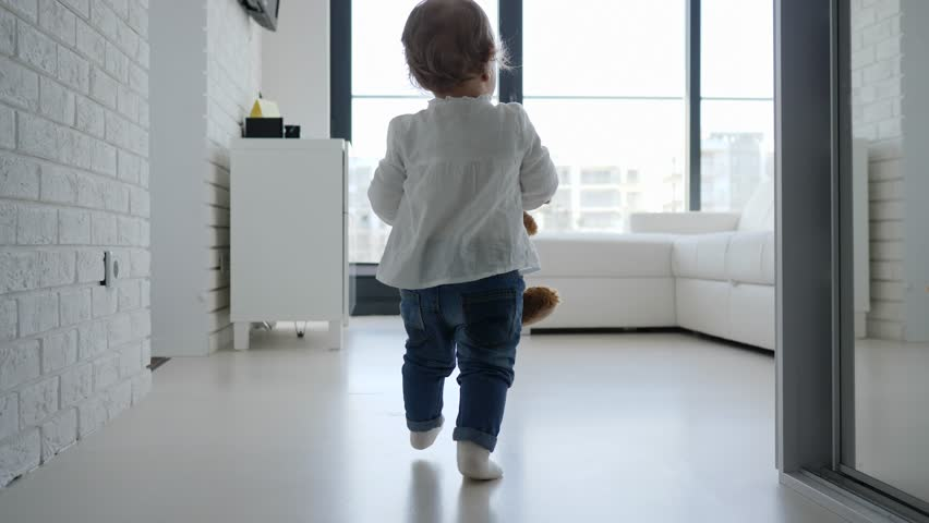 Holding plush toy baby child girl legs in jeans walking at home #1024400345