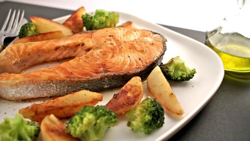 Meal with salmon fish steak and vegetable. Bottle of Olive oil pouring on salmon fish. Healthy food. Main course Close up. Slow motion video footage. Slowmo. Slow-mo