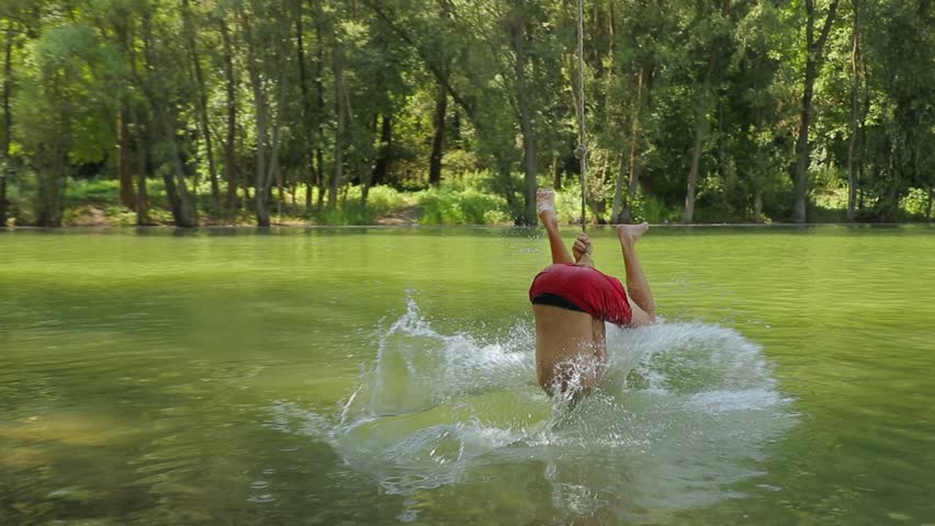 Guy jumping from rope swing hitting the water face first | Shutterstock HD Video #1024402967