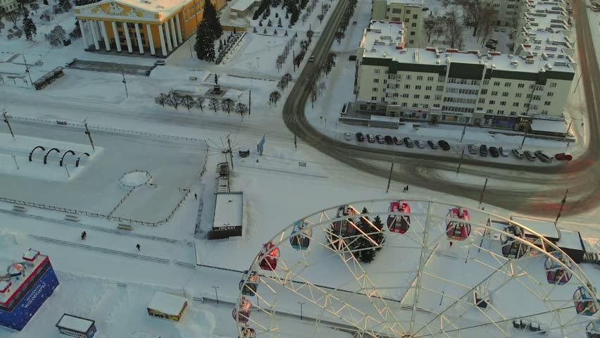 Aerial view of the city square, ferris wheel and residential buildings next to the frozen river in the city. Aerial shooting, cityscape at sunset, sunrise | Shutterstock HD Video #1024410365