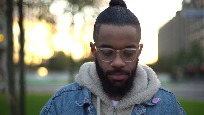 Slow-mo handsome charismatic black bearded hipster university student wearing glasses standing city centre, walking downtown, looking camera licking lips smiling happy, delighted sweet words | Shutterstock HD Video #1024412981