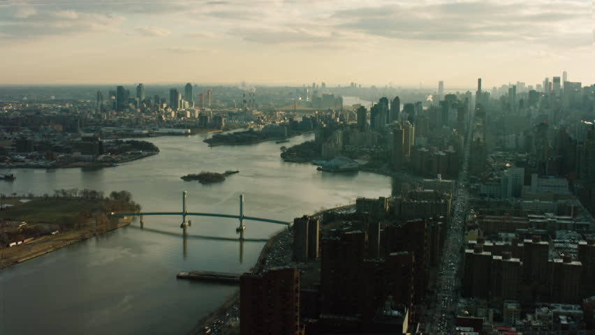 Aerial view of East River heading towards downtown Manhattan, New York City in bright lighting with lens flares. Wide shot. 4k shot with a RED camera.