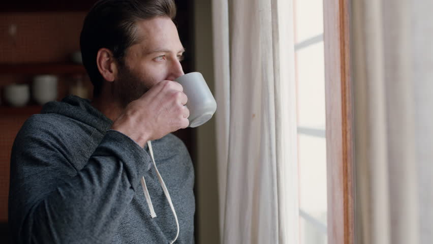 Young man opening curtains looking out window enjoying fresh new day feeling rested drinking coffee at home
