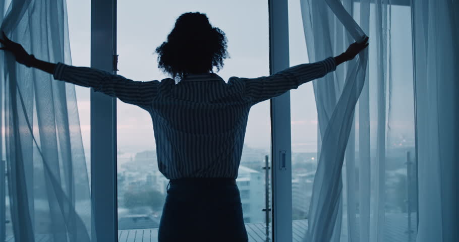 business woman opening curtains in hotel room looking out window at fresh new day successful independent female planning ahead on cloudy morning #1024427900