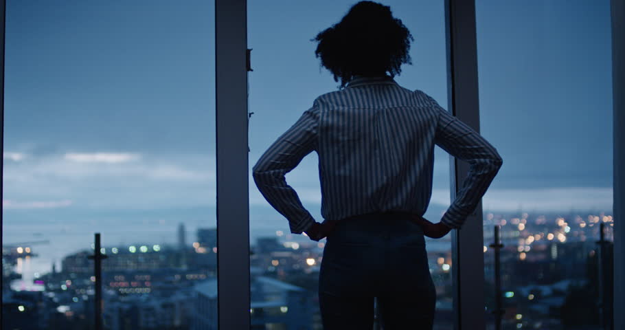 young woman looking out window enjoying view of city at night contemplating successful lifestyle planning ahead on calm urban evening Royalty-Free Stock Footage #1024427906