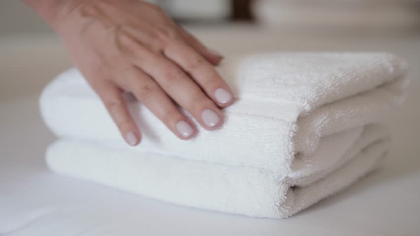 Close-up of hands putting stack of fresh white bath towels on the bed sheet. Room service maid cleaning hotel room macro closeup