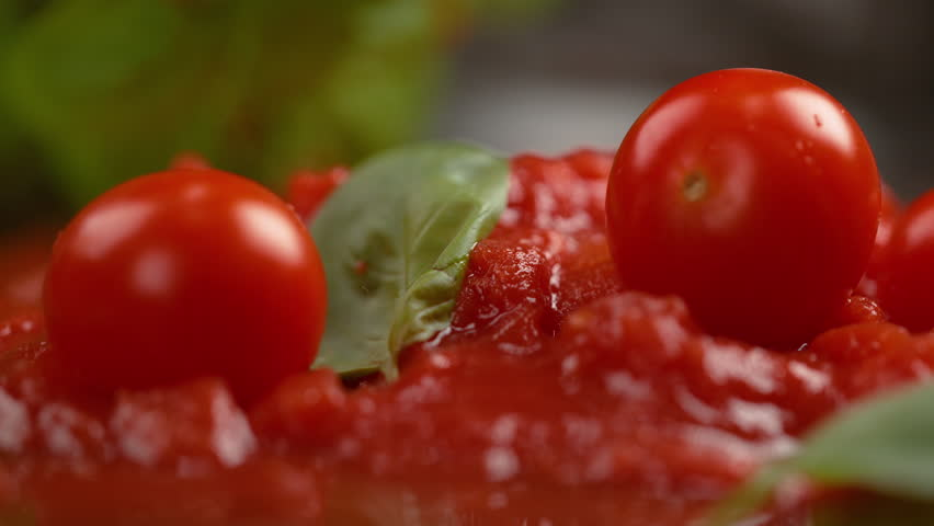 SLOW MOTION, MACRO, DOF: Small tomatoes fall into the fresh vegetarian tomato sauce with basil. Delicious marinara splatters across the table as cherry tomatoes are dropped into the cooked sauce.