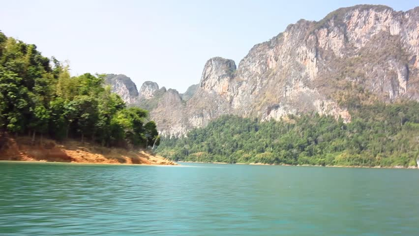 Boat trip on the blue water of Cheo Lan Lake in Thailand among rocks and jungle on a summer day | Shutterstock HD Video #1024466477
