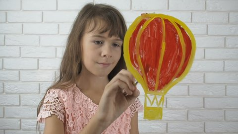 The child draws on the glass. A little girl paints a balloon.